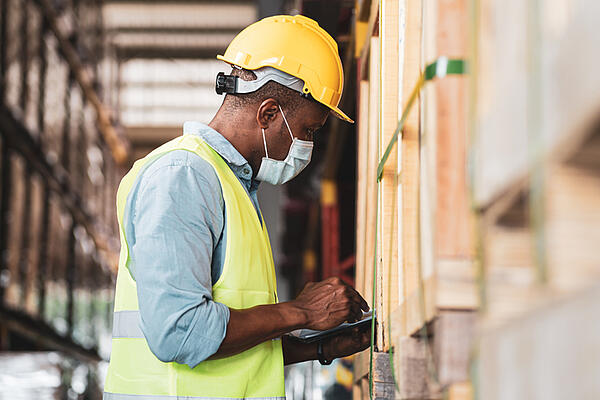 Man working in a warehouse with hard hat and facemask, looking at a tablet