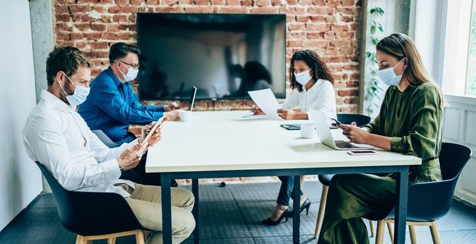four gender and ethnically diverse people sitting in a meeting with facemasks on